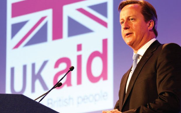 David Cameron speaks in front of the UK Aid logo