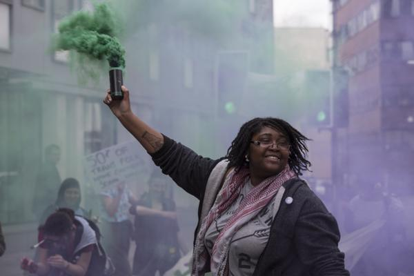 A woman of colour activist smiles whilst holding up a green smoke bomb. A crowd is visible behind them. They are attending the Sisters Uncut action da.y.