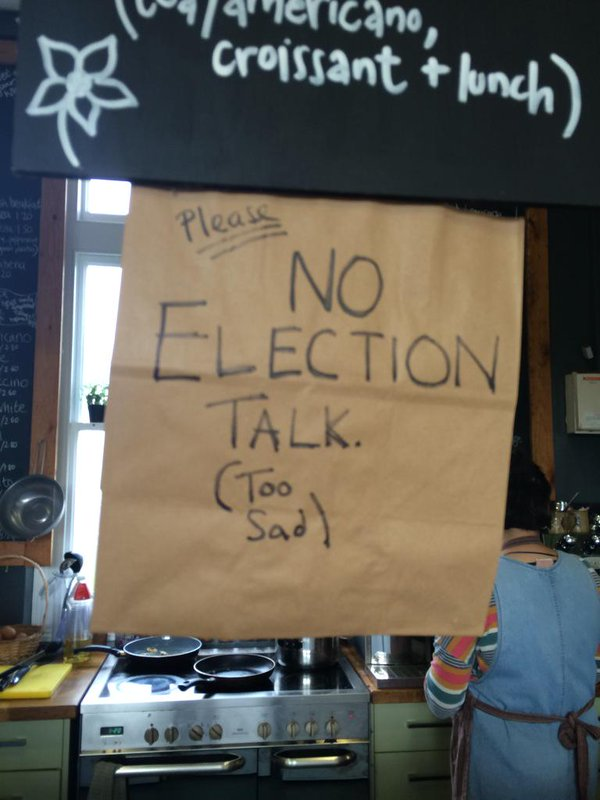 "A handwritten sign with the words ""Please no election talk. (Too sad)"" hanging below a cafe menu"