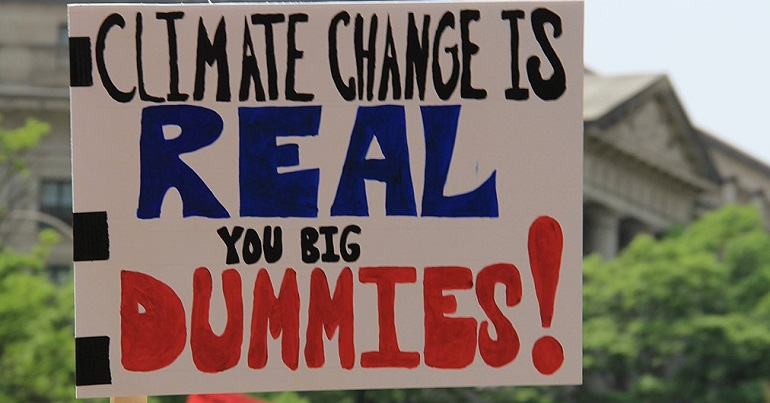 Placard reading: climate change is real you big dummies