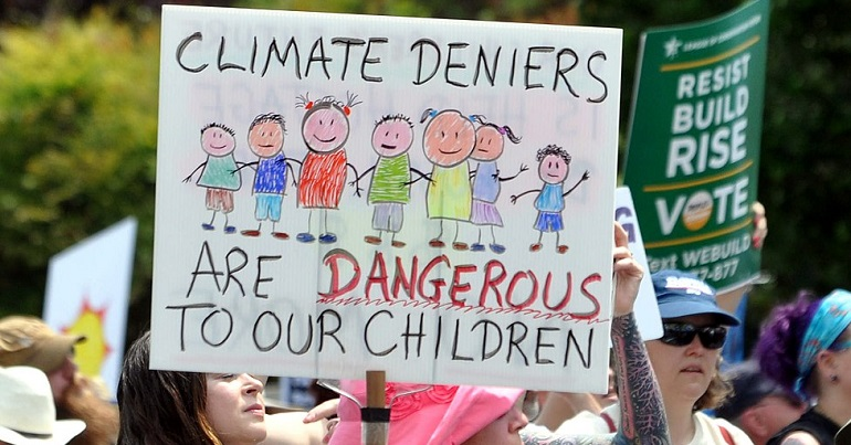 """Climate change protest placard reads: """"Climate deniers are dangerous to our children"""""""