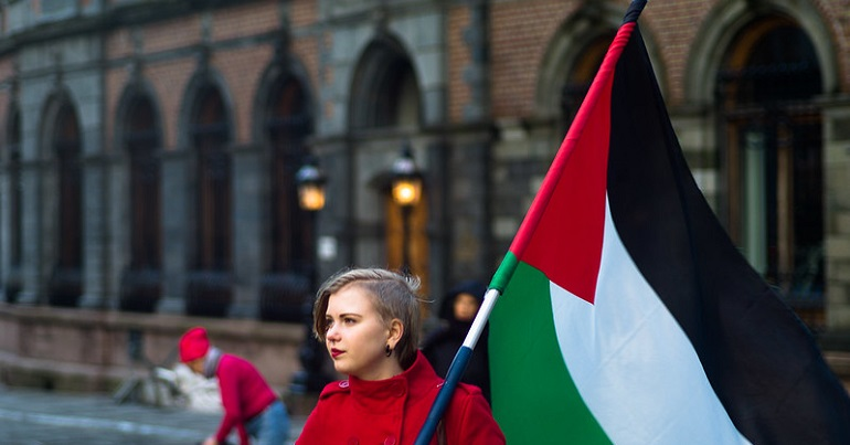 Young woman carrying a Palestinian flag