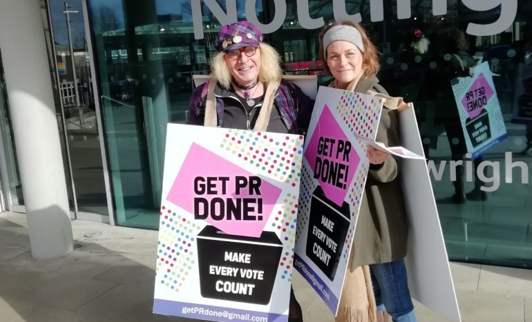 """Two protesters with sandwich board placards reading """"Get PR Done"""""""