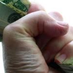 A hand grasping money